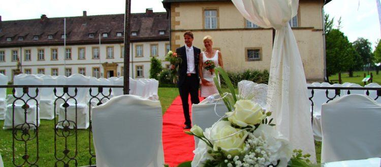 Braut und Bräutigam schreitet auf dem roten Teppich zur Trauung.