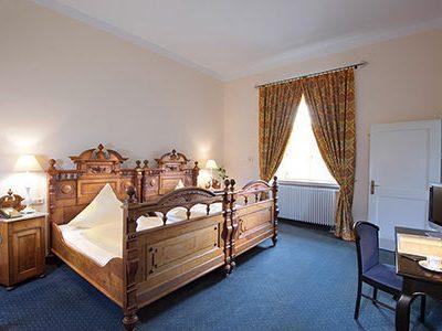 Doppelzimmer mit kunstvollem Holzbett.